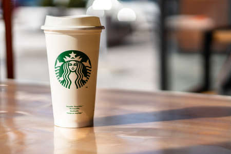 Slovenia 27.2.2019 - Starbucks take away, hot beverage coffee cup with logo, on the table in store.