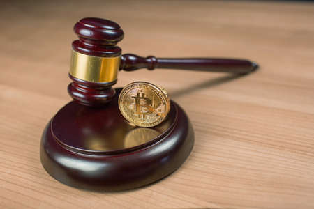 Photo for Bitcoin regulation. BTC cryptocurrency coin and judge gavel on a desk. Banned currency or law enforcement concept. - Royalty Free Image