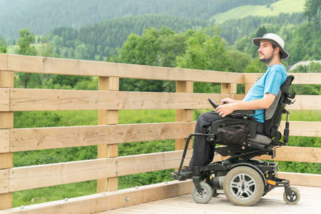 Photo for disabled Young man in electric wheelchair on a boardwalk enjoying his freedom and observing nature - Royalty Free Image