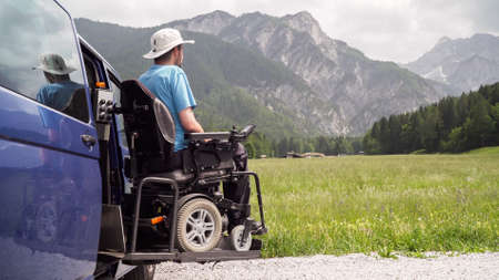 Photo for electric lift specialized vehicle for people with disabilities. Empty wheelchair on a ramp with nature and mountains in the back - Royalty Free Image