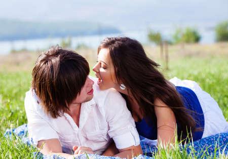 Photo pour Two lovers lying on the grass near mountain lake - image libre de droit