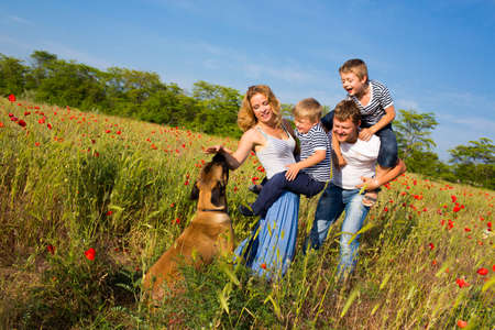 Photo for Family of four person playing on the poppy field - Royalty Free Image