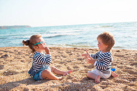 Little boy and girl playing on the beach