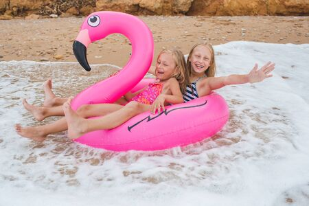 Photo pour Girls are playing on the beach with an inflatable flamingo. the hit of the season. two sisters - image libre de droit