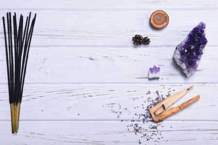 Composition of esoteric objects used for healing, meditation, relaxation and purifying. Amethyst stones, palo santo wood, Aromatic scent sticks on white background.
