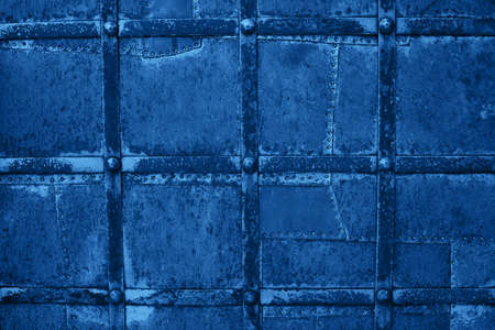 Top view of worn rusty squared metal background texture n blue color. Trendy color background.