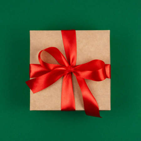 Photo for Top view of craft Merry Christmas gift with red bow ribbon over green background. Happy New Year greetings. Festive winter holidays backdrop. Flat lay. Happy Birthday card. - Royalty Free Image