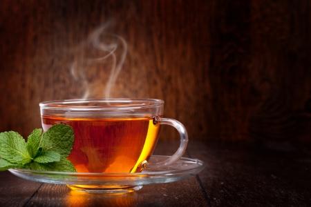 Photo pour Cup of tea and mint on a wooden background - image libre de droit