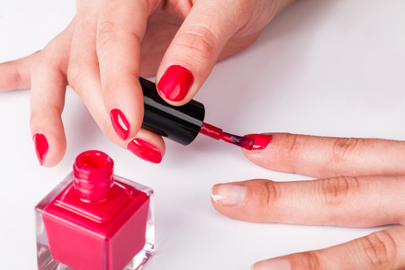 Painting polish on fingers with red nails