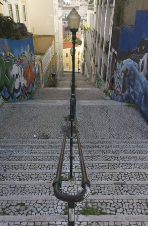 LISBON, PORTUGAL - OCTOBER 25 2014: Calcada do Lavra street in Lisbon, with its staircase and graffiti, with light pole in the middle