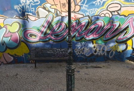 LISBON, PORTUGAL - OCTOBER 25 2014: A bench and a light pole in Calcado do Lavra street in Lisbon, full with graffiti on the wall