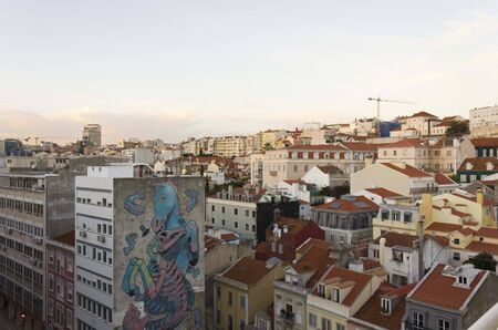 LISBON, PORTUGAL - OCTOBER 23 2014: View from the top of downtown Lisbon at sunset time, with a big seahorse mural on a building facade