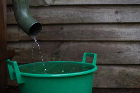 Foto für Rainwater shooting from a gutter into a water collecting reservoir - Lizenzfreies Bild