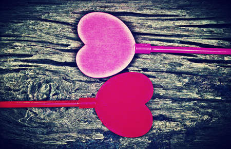 Vintagephoto of pink and red hearts on wood background.