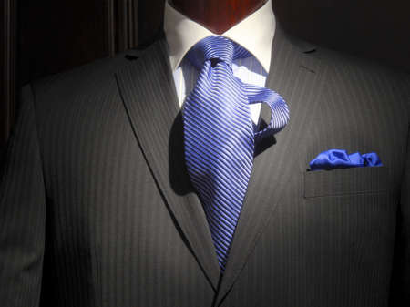Close-up of a dark grey striped jacket with blue striped shirt with white collar, striped blue tie and blue handkerchief