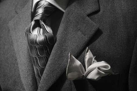 Close up of a grey jacket with grey tie & handkerchief