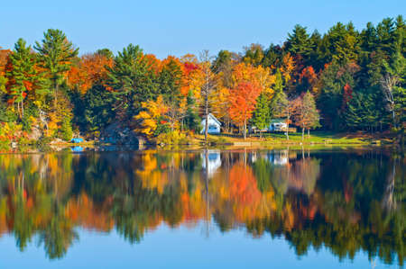Autumn landscape with colourful trees reflecting in a calm lake.