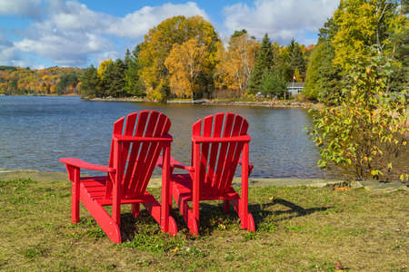Two red Adirondack Chairs on a lake shore on a sunny autumn day