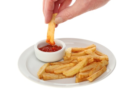 Hand dipping a French fry into tomato ketchup in a ramekin next to fries on a plate isolated against white