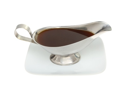 Meat gravy in a stainless steel gravy boat on a plate isolated against white