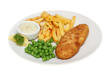 Battered fish, chips and peas with tartar sauce and a garnish of lemon and parsley on a plate isolated against white
