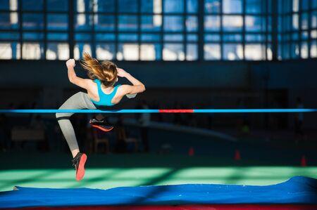Photo for Woman jumping over bar at athletics meeting - high jump discipline - Royalty Free Image