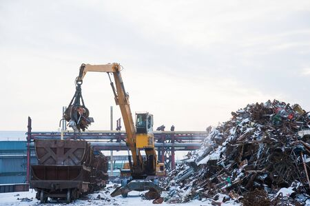 Photo pour Scrap metal recycling plant and crane-loading scrap in a train - image libre de droit