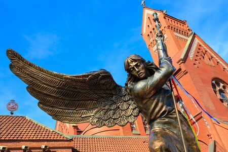 Statue of Archangel Michael with outstretched wings, thrusting a spear into a dragon before the Catholic Church of St. Simon and St. Helena.