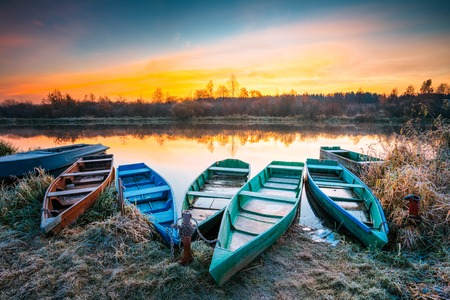 Lake, River and rowing fishing boat at beautiful sunrise in autumn morning. Old wooden boats and frosted grass.
