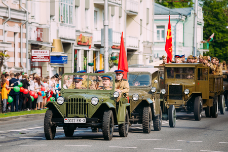 Gomel, Belarus - May 9, 2016: The Moving Column Parade Of Russian Soviet Military Cars Trucks Of WW2 Time With People In Soldiers Uniform On Boards With Red Flags. Celebrating The Victory Day Holiday