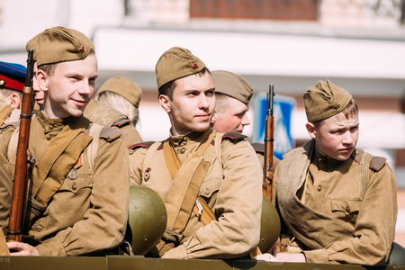 Gomel, Belarus - May 9, 2016: Close View Of Young Men In Soldiers Soviet Uniform With Guns Of WW2 Time Sitting In Military Truck. The Participants Of Parade Celebrating The Victory Day In Homiel.