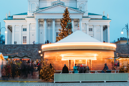 Helsinki, Finland. Xmas Market On Senate Square With Holiday Carousel And Famous Landmark Is Lutheran Cathedral And Monument