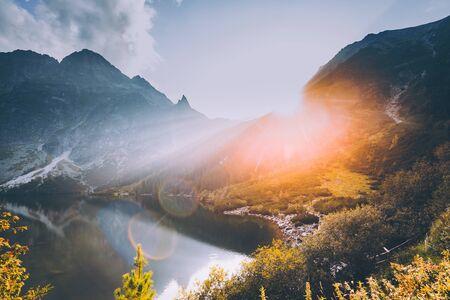 Photo for Tatra National Park, Poland. Famous Mountains Lake Morskie Oko Or Sea Eye Lake In Summer Evening. Beautiful Sunset Sun Sunshine Sunbeams Above Tatras Lake Landscape - Royalty Free Image
