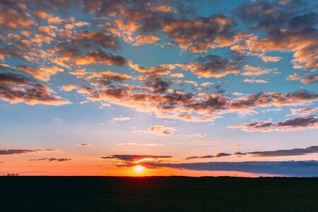 Photo pour Natural Sunset Sunrise Over Field Meadow. Bright Dramatic Sky And Dark Ground. Countryside Landscape Under Scenic Colorful Sky At Sunset Dawn Sunrise. Skyline, Horizon. Warm Colours. - image libre de droit
