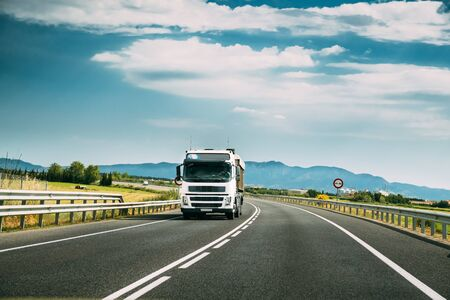 Photo pour White Truck Or Traction Unit In Motion On Road, Freeway. Asphalt Motorway Highway Against Background Of Mountains Landscape. Business Transportation And Trucking Industry. - image libre de droit