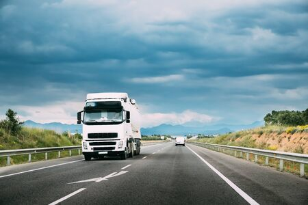 Photo for White Truck Or Traction Unit In Motion On Road, Freeway. Asphalt Motorway Highway Against Background Of Mountains Landscape. Business Transportation And Trucking Industry. - Royalty Free Image