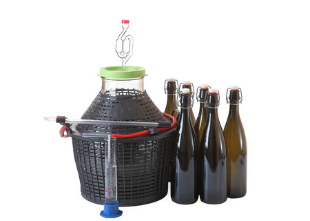Set of equipment for home winemaking, carboy with a hose, airlock, wine bottles of dark glass with plastic caps and rubber seal, hygrometer, isolated image on white background.