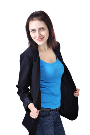 Vertical portrait of one young smiling caucasian woman, 18 years old, dressed in a dark blue office jacket, light blue tank top and jeans trousers, isolated on white background.