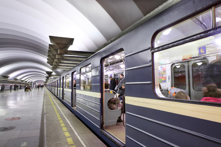 St. Petersburg, Russia - March 7,  2014: Passenger platform at a subway station, train with blue wagons standing with open doors. Deep underground station Ploshchad' muzhestva.
