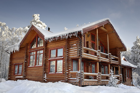 Log cabin with large windows, balcony and porch, modern house design, snowy winter, sunny day.