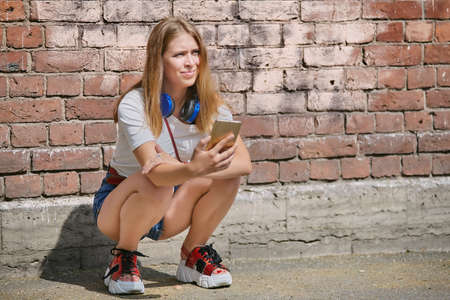 Photo pour Woman in her 20s is squatting near brick wall with mobile phone in her hand. A young blonde uses a smartphone while walking around the city. - image libre de droit