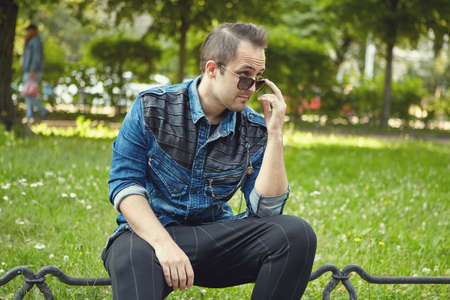 Foto de Young white man in sunglasses is sitting in the public park at the daytime. Caucasian male is walking outdoors. - Imagen libre de derechos