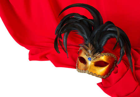 Venetian mask with black feathers on red fabric