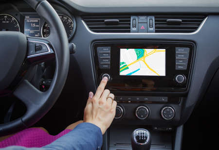 Photo pour Woman using navigation system while driving a car - image libre de droit