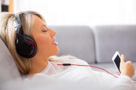 Photo pour Relaxed woman listening to music on headphones at home - image libre de droit