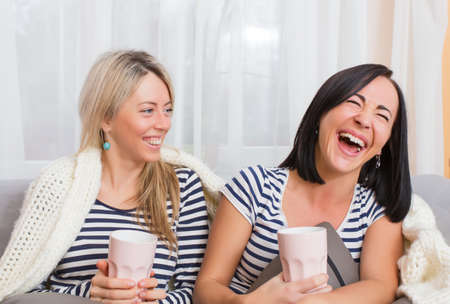 Two cheerful women laughing while sitting comfortably in bed