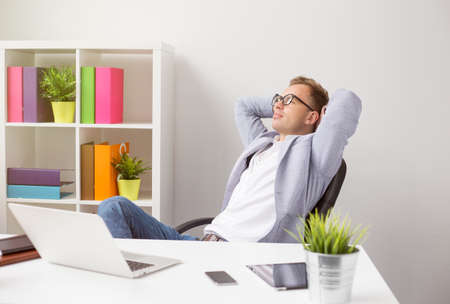 Relaxed businessman sitting in chair with hands behind head