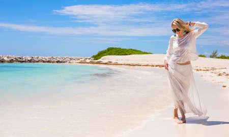 Foto de Young happy woman walking on the beach - Imagen libre de derechos