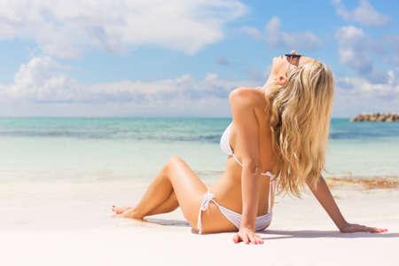 Photo pour Woman relaxing on the beach - image libre de droit