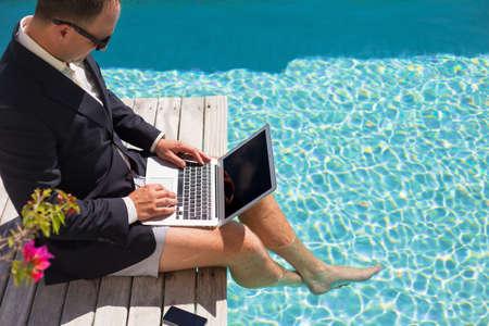 Photo pour Businessman working with laptop computer by the pool - image libre de droit